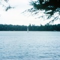 A sailboat races across Lake Machkinosiew (Enterprise Lake).
